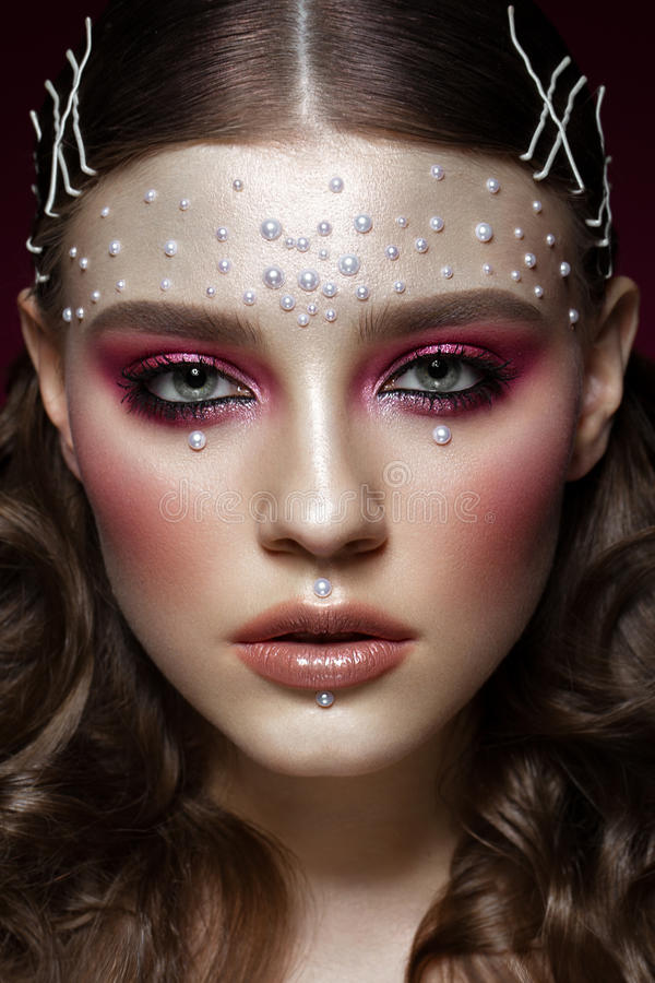 Beautiful girl with perfect art makeup and pearl beads. beauty face. Photos shot in the studio stock images