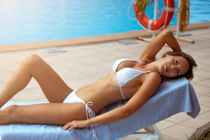 A beautiful girl with a perfect slim figure in a white bikini swimsuit is relaxing on sunbed by pool. A beautiful girl with a perfect slim figure in a white royalty free stock photography
