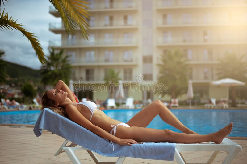 A beautiful girl with a perfect slim figure in a white bikini swimsuit is relaxing on sunbed by pool. A beautiful girl with a perfect slim figure in a white stock photography