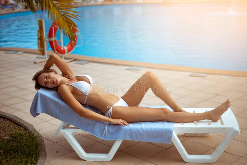 A beautiful girl with a perfect slim figure in a white bikini swimsuit is relaxing on sunbed by pool. A beautiful girl with a perfect slim figure in a white stock photos