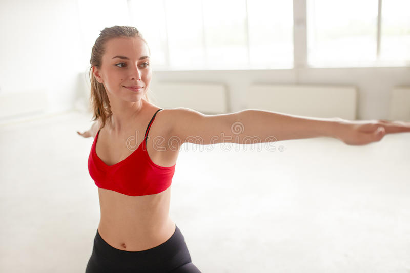Beautiful girl performing yoga in warrior pose stock photography