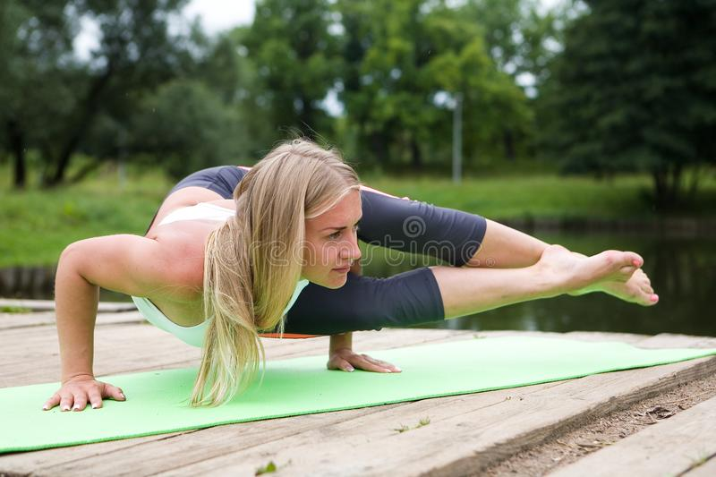 A beautiful girl performs a stand on the arms of Ashtavakrasana. royalty free stock image