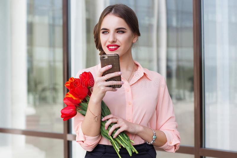 Beautiful girl with phone and flowers royalty free stock photography