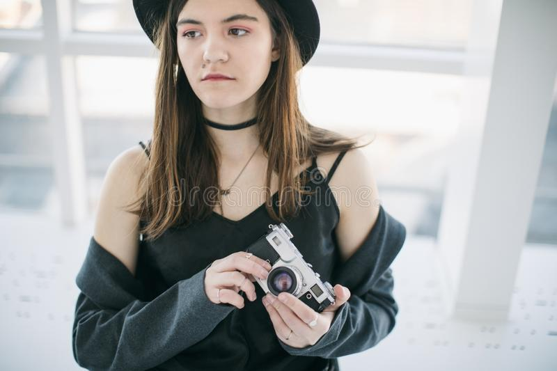 Beautiful girl photographer in stylish hipster clothes. Creative profession royalty free stock images