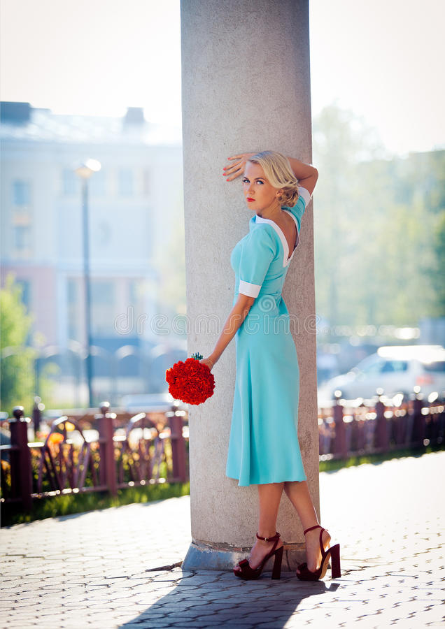Beautiful girl in a pink dress with a bouquet of royalty free stock photos