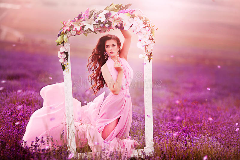 Beautiful girl in a pink dress flying in a lavender field stock photos