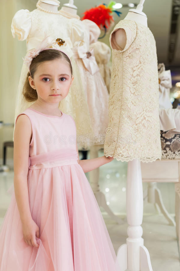 Beautiful girl in a pink dress in a modern store stock photography