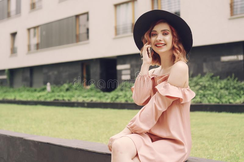 Beautiful girl in a pink dress sitting near high-rise buildings . Girl speaks by phone. Woman with pink hair in a black hat stock image