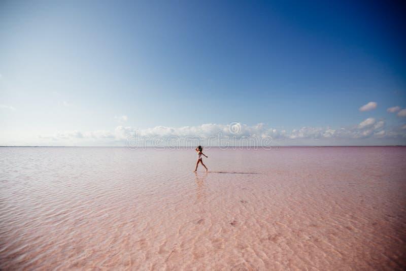 Beautiful girl on a pink lake. royalty free stock photos