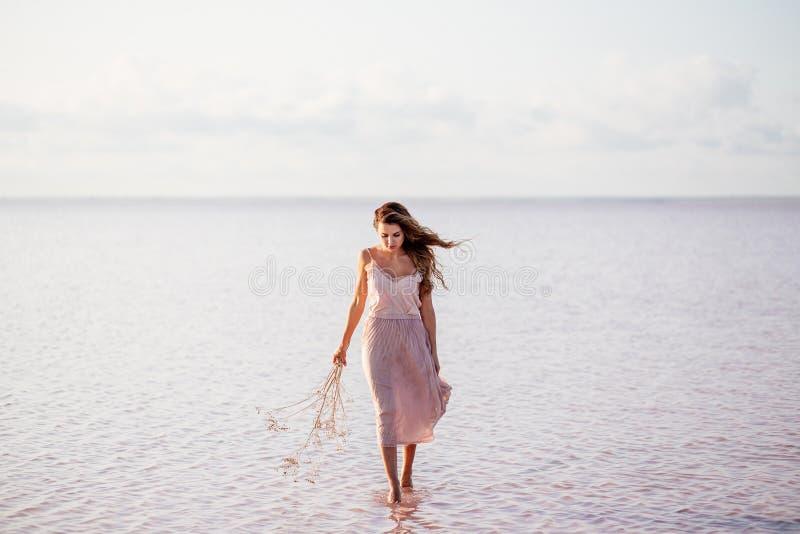 Beautiful girl on a pink lake. stock photos