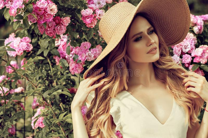 Beautiful girl in pink vintage dress and straw hat standing near colorful flowers. Art work of romantic woman stock photos