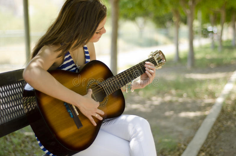 Beautiful girl playing a guitar. Cute young woman playing the guitar in a park bench royalty free stock images