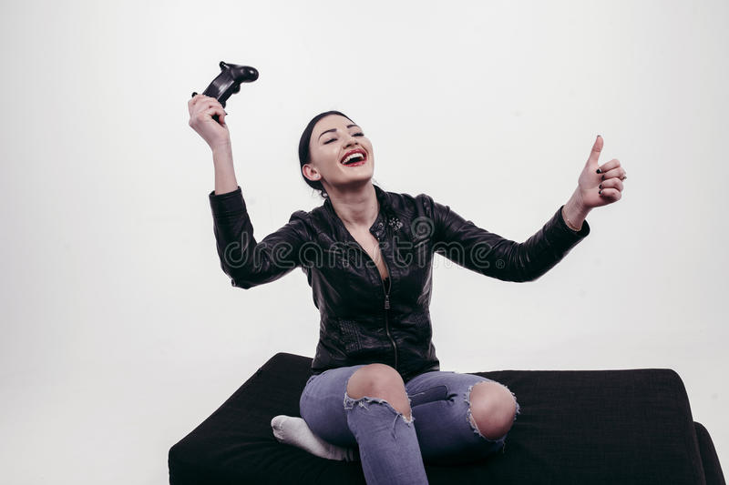 Beautiful girl playing with joystick in black jacket stock images