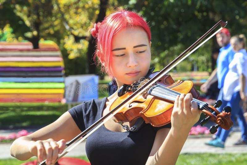 Beautiful girl playing the violin in a city park on a sunny day. Portrait royalty free stock photos