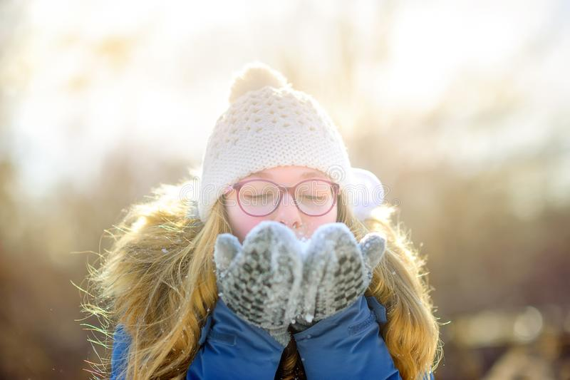 Beautiful girl plays in a snowy park, blows snowflakes from her hands. royalty free stock photo