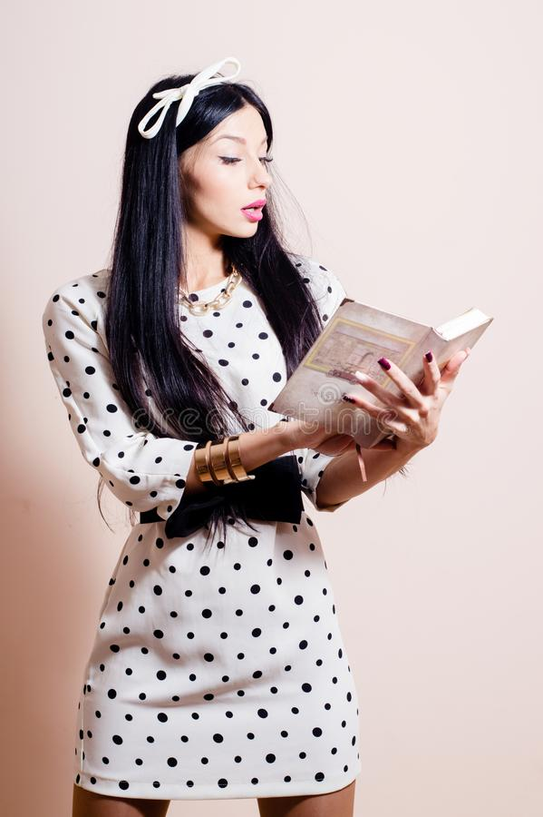 Beautiful girl in polka dot white dress reading. Portrait of beautiful young woman in polka dot white dress reading book royalty free stock photo