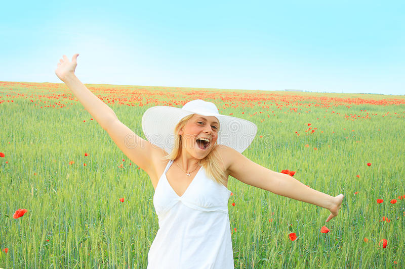 Beautiful girl in the poppy field royalty free stock image