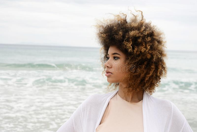 Beautiful girl portrait with afro hair and white dress relax on. The beach stock images