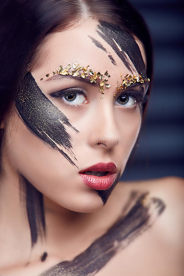 Beautiful girl portrait with creative art make up. With black paint lines.Woman with make-up and gold pieces sequins. Plump red lips royalty free stock images