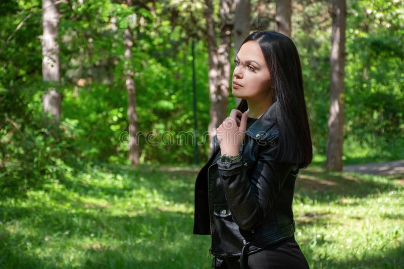 Beautiful girl portrait in the forest on a spring day. Woman with black hairstyle and wears a leather jacket stock images