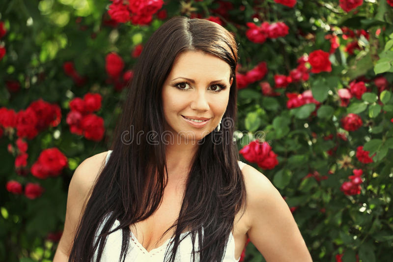 Beautiful girl portrait on the red roses. Beautiful girl portrait on the background of red roses royalty free stock images