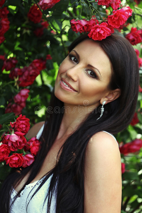 Beautiful girl portrait on the red roses. Beautiful girl portrait on the background of red roses royalty free stock photo