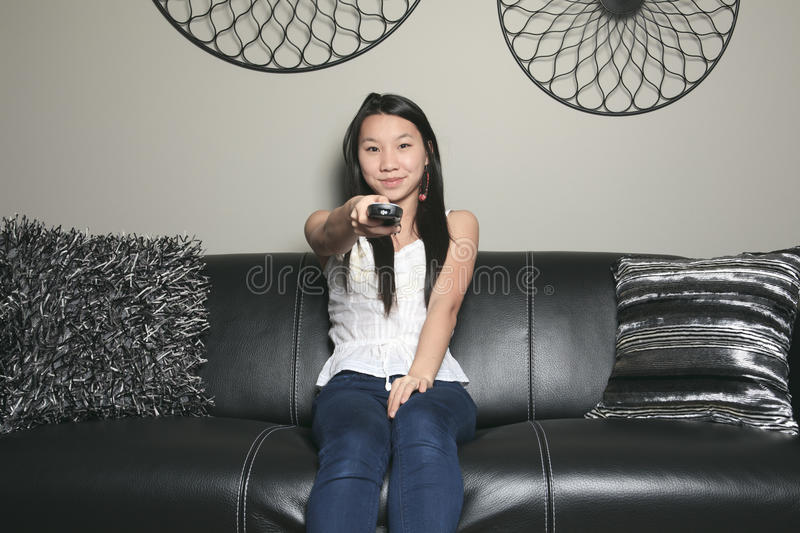 Beautiful girl portrait sitting in the sofa of a. A beautiful girl portrait sitting in the sofa of a living room with remote control royalty free stock images