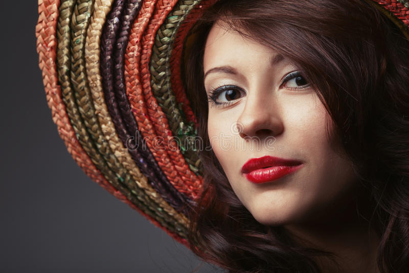 Beautiful girl portrait with sombrero. On grey background royalty free stock photography