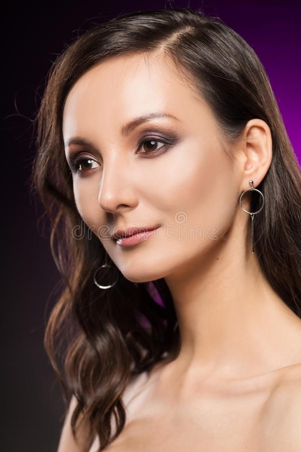 The beautiful girl portrait on a violet background. Mixed asian-caucasin race. Naked shoulders. Evening make-up. Clean healthy skin. Close-up stock photography
