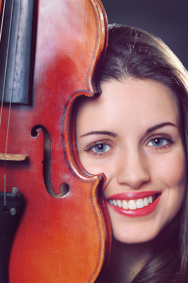 Beautiful girl portrait with a fiddle. Beautiful girl portrait with a violin detail . Model is smiling royalty free stock images