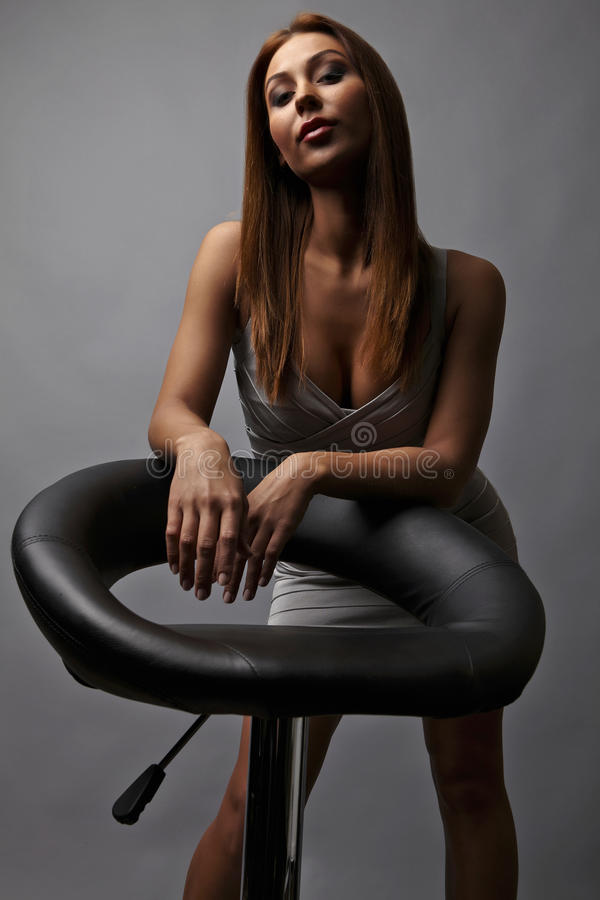 Beautiful girl pose near stylish armchair. Photo.