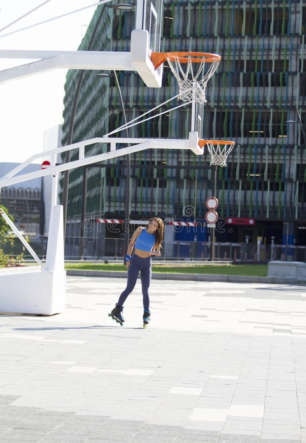 Cute girl, handsome, fit sporty, poses, inline skate on basketball court.. Beautiful girl poses. Above she it we see hoops basketball. In the background we see royalty free stock photography