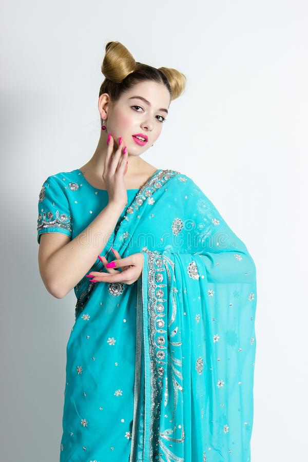 Beautiful girl poses in blue sari. Looks like a doll and indian woman. royalty free stock images