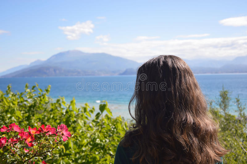 Beautiful girl posing back with natural lake mountains landscape with flowers and trees, woman model in nature.  royalty free stock photography