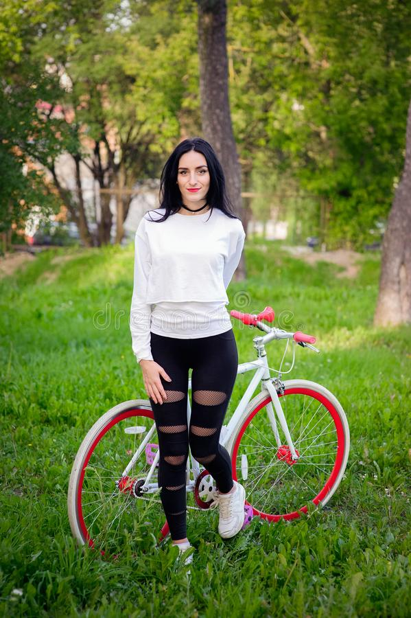 Beautiful girl posing on a bicycle. white and red bike. walk in nature. healthy lifestyle. weekend in nature Portrait of a happy. Beautiful girl in a white T stock photography