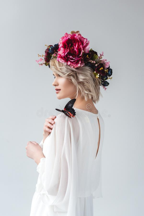 Beautiful girl posing in flower wreath with butterfly on shoulder,. Isolated on grey stock photo