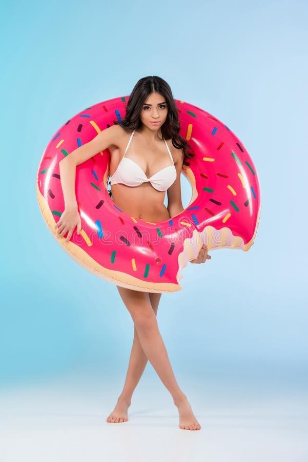 Beautiful girl posing with inflatable donut ring,. Isolated on blue royalty free stock photography