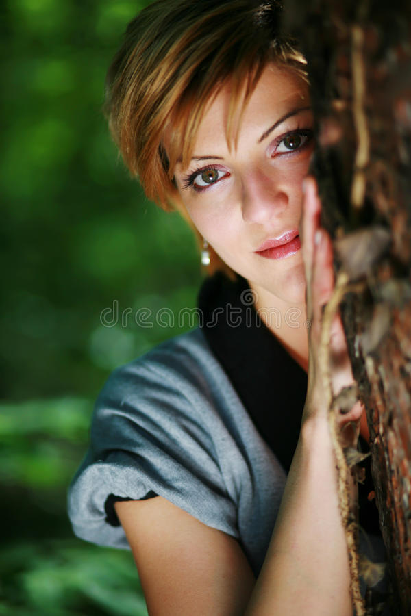 Beautiful girl posing leaning on a tree. Beautiful girl posing in front of the camera in the forest leaning on a tree royalty free stock images