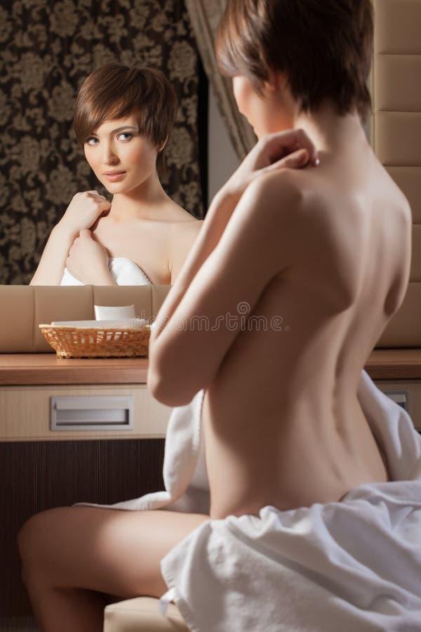 Beautiful girl posing naked near mirror. Close-up stock image