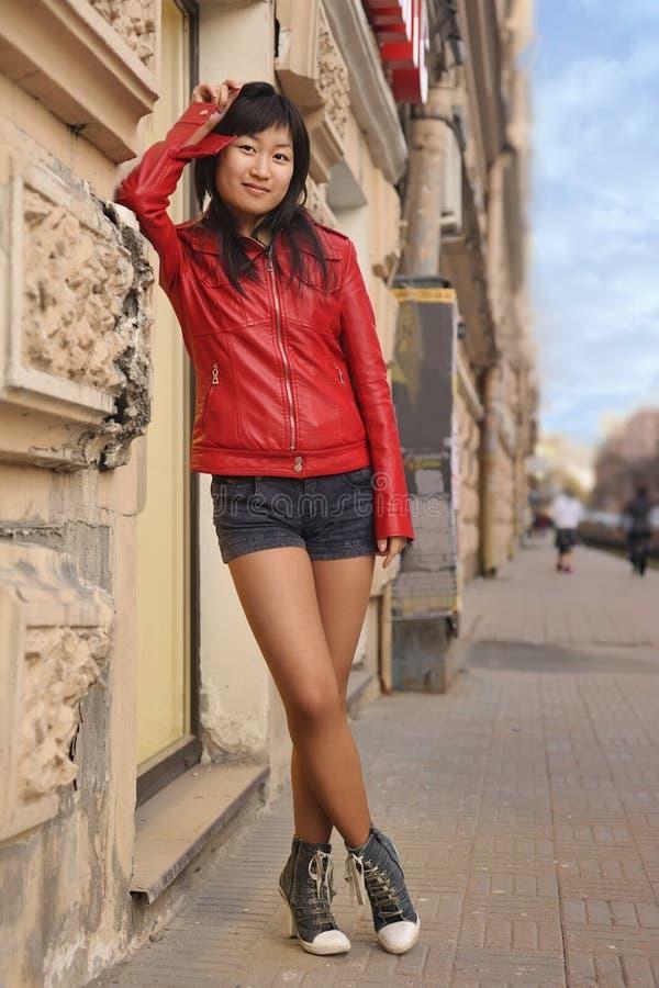 Beautiful girl posing near wall. Beautiful girl posing on street near wall stock image