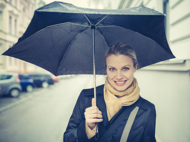 Beautiful Girl Is Posing at Street Holding an Umbrella. During a Spring Rainy Weather royalty free stock images