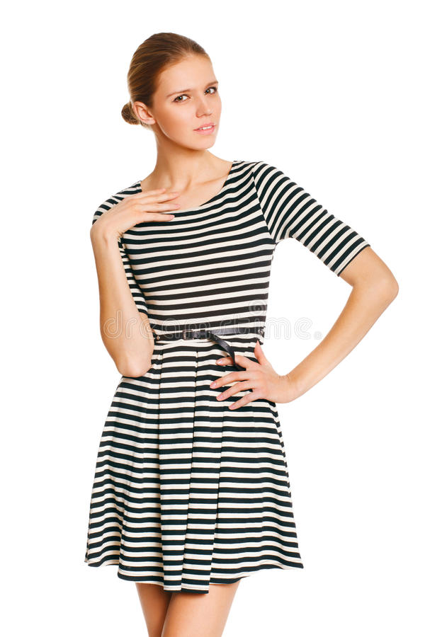 Beautiful girl posing in striped white dress with hand on hip against white background royalty free stock photography