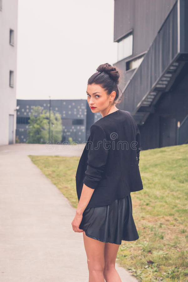 Beautiful girl posing in an urban context. Gorgeous young brunette in black skirt posing in an urban context royalty free stock photo