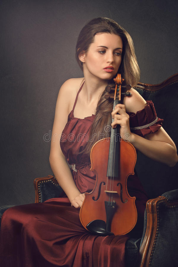 Beautiful girl posing with a violin. Beautiful girl posing with a fiddle seated on a velvet armchair . Textured backdrop stock photo