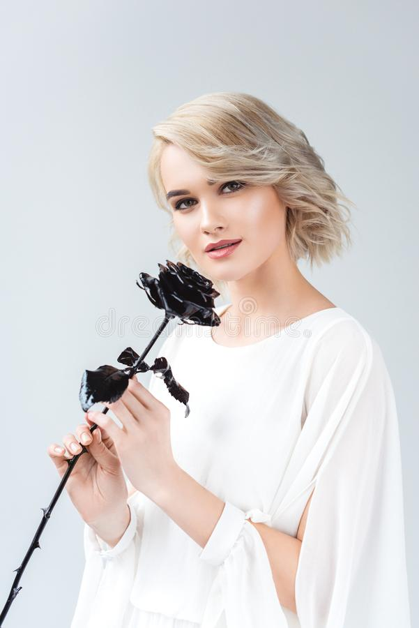 beautiful girl posing in white blouse with black rose, royalty free stock image