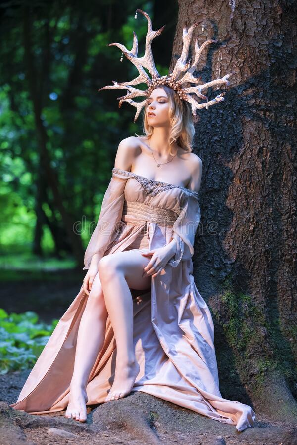 Free Beautiful Girl Posing With Artistic Deer Horns  In Summer Forest Near High Tree. Wearing Light Dress For Forest Nymph Concept. Art Stock Photo - 191850880