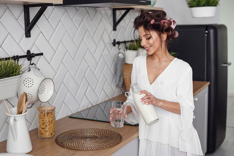 Beautiful girl pours milk from a carafe into a glass, in the stylish cozy kitchen. Healthy eating and diet concept. royalty free stock photography