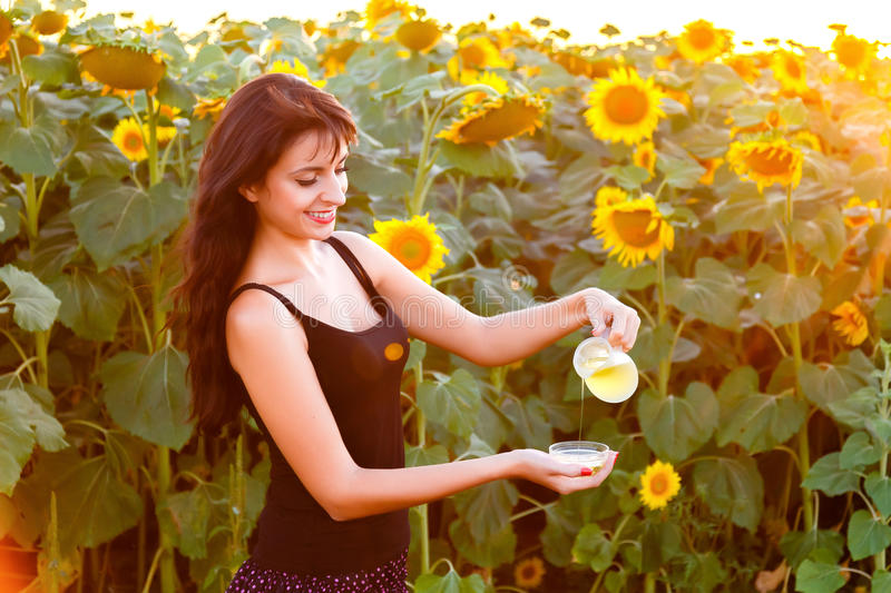 Beautiful girl pours sunflower oil from the pitcher stock image