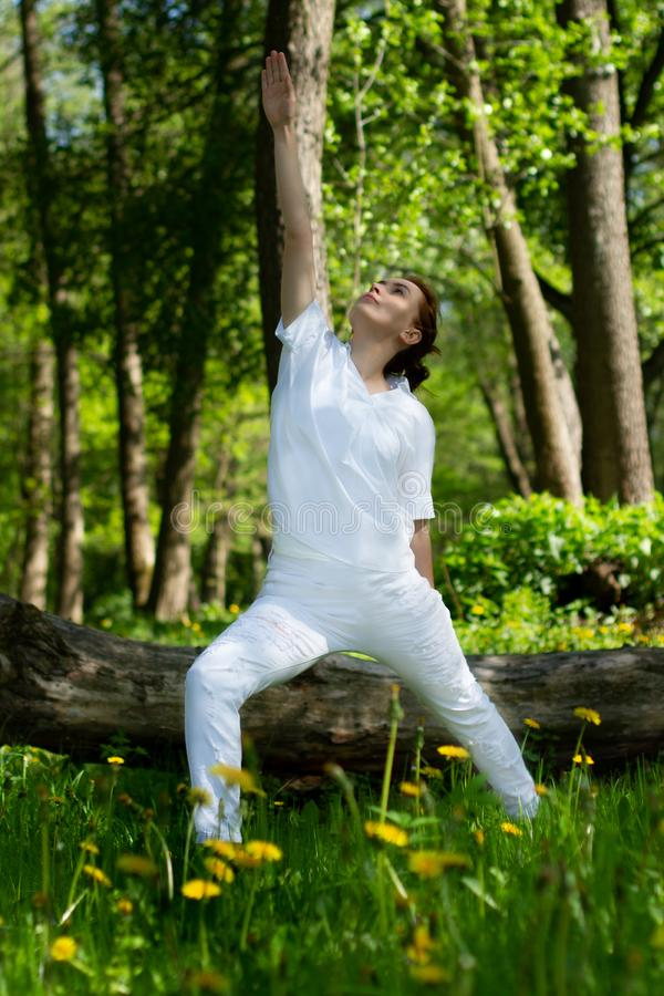 Beautiful girl practices yoga in peaceful nature atmosphere royalty free stock photo