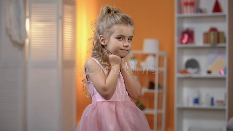 Beautiful girl in princess dress posing for camera, event center, celebration stock photo